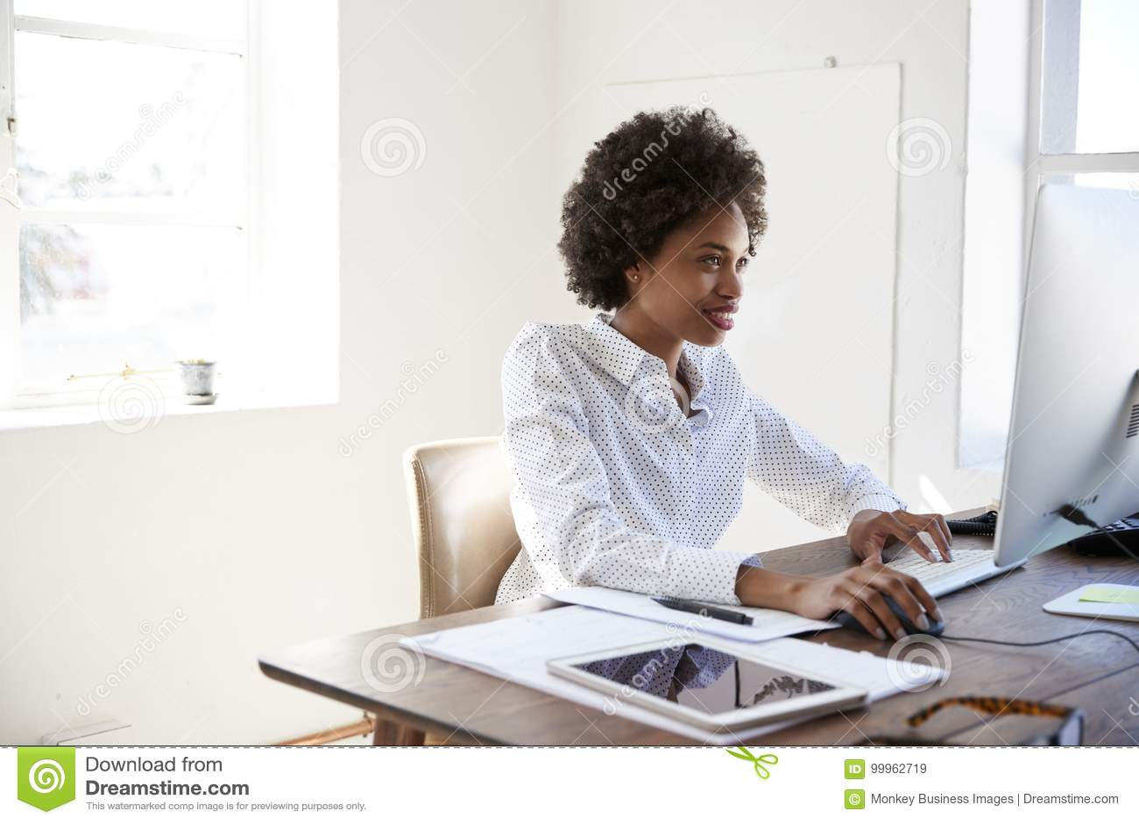 Ung svart kvinna som arbetar på datoren i ett kontor, slut upp