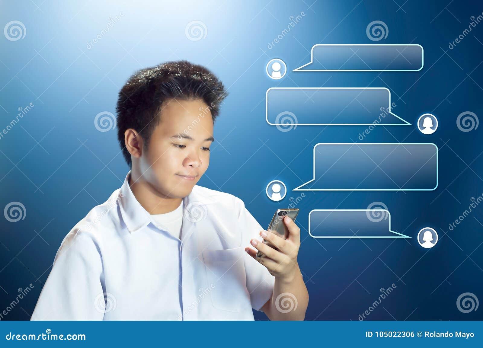 Ung tonåringstudent Texting som använder hans Smartphone med den projekterade konversationasken