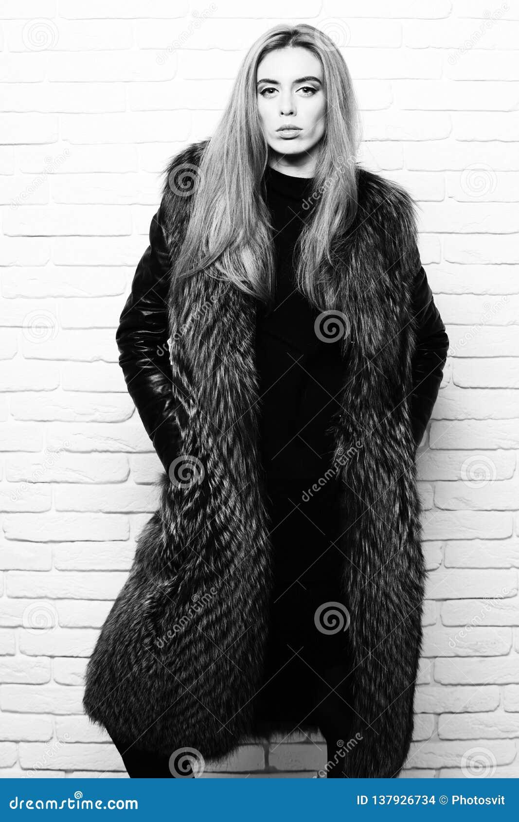 Ung trendig nätt kvinna eller flicka med härligt långt blont hår i midjalag av burgundy päls med svart