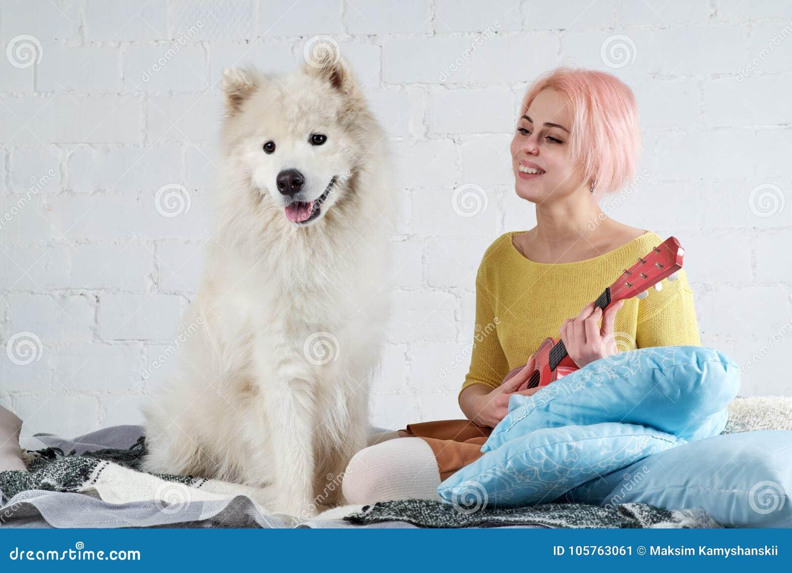 Ung vänlig glad flicka som spelar ukulelet, gitarrsittien