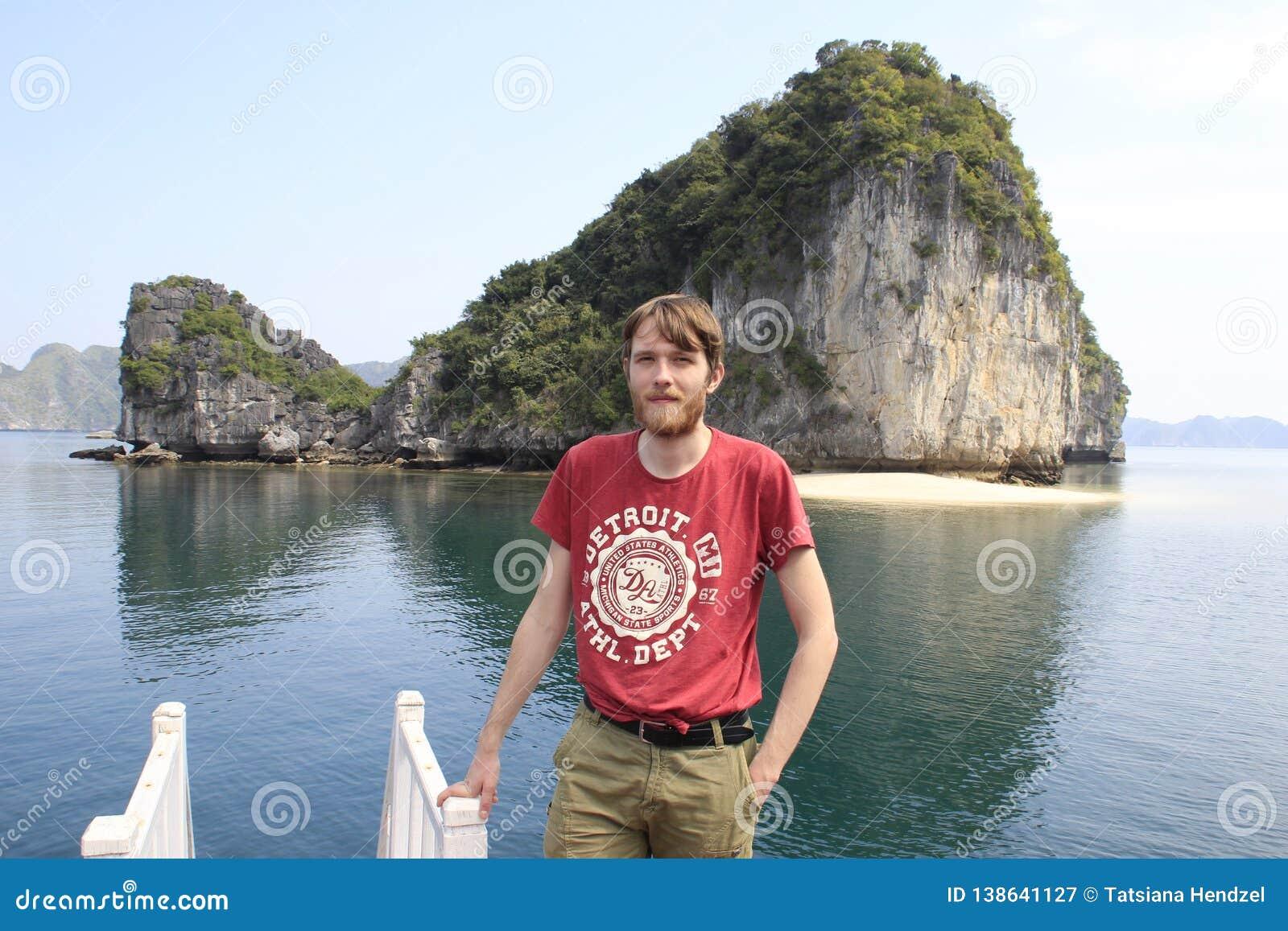 Ung vit attraktiv man som är blond med ett skägg i en röd t-skjorta mot bakgrunden av en klippa och havet i lång fjärd för mummel
