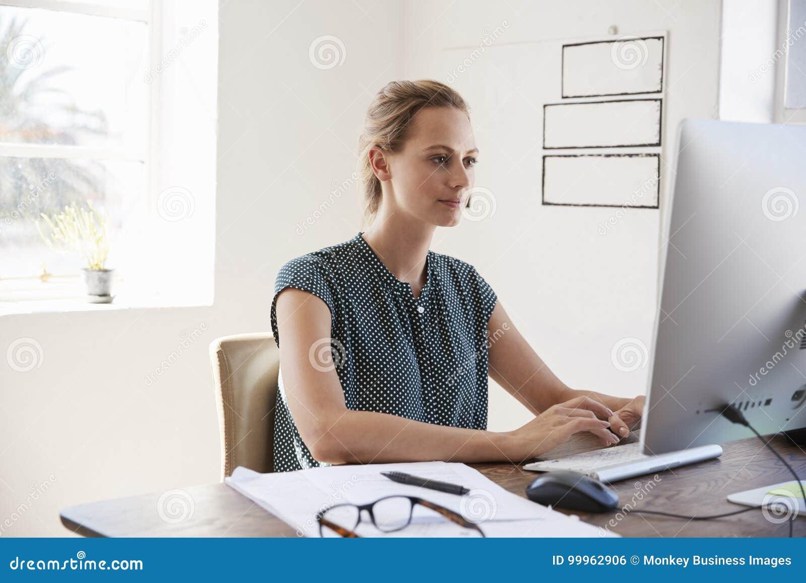 Ung vit kvinna som i regeringsställning arbetar genom att använda upp datoren, slut