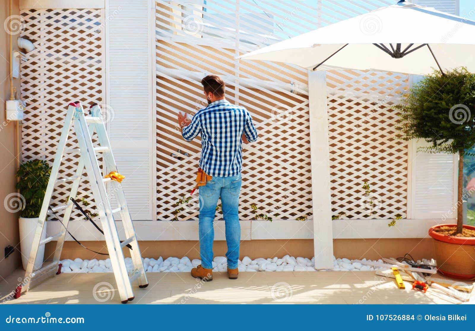 Ung vuxen man som bygger träpergolaväggen på takuteplatszon