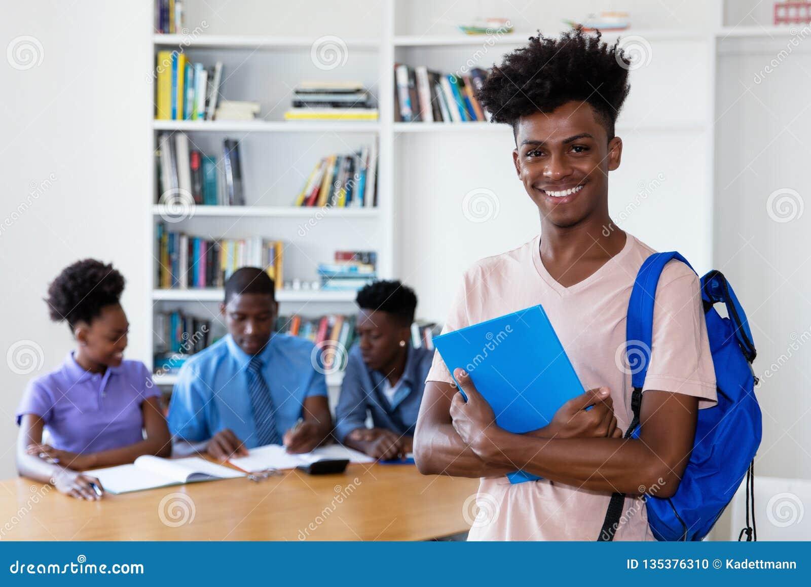Ung vuxen student för afrikansk amerikan med grupp på skola