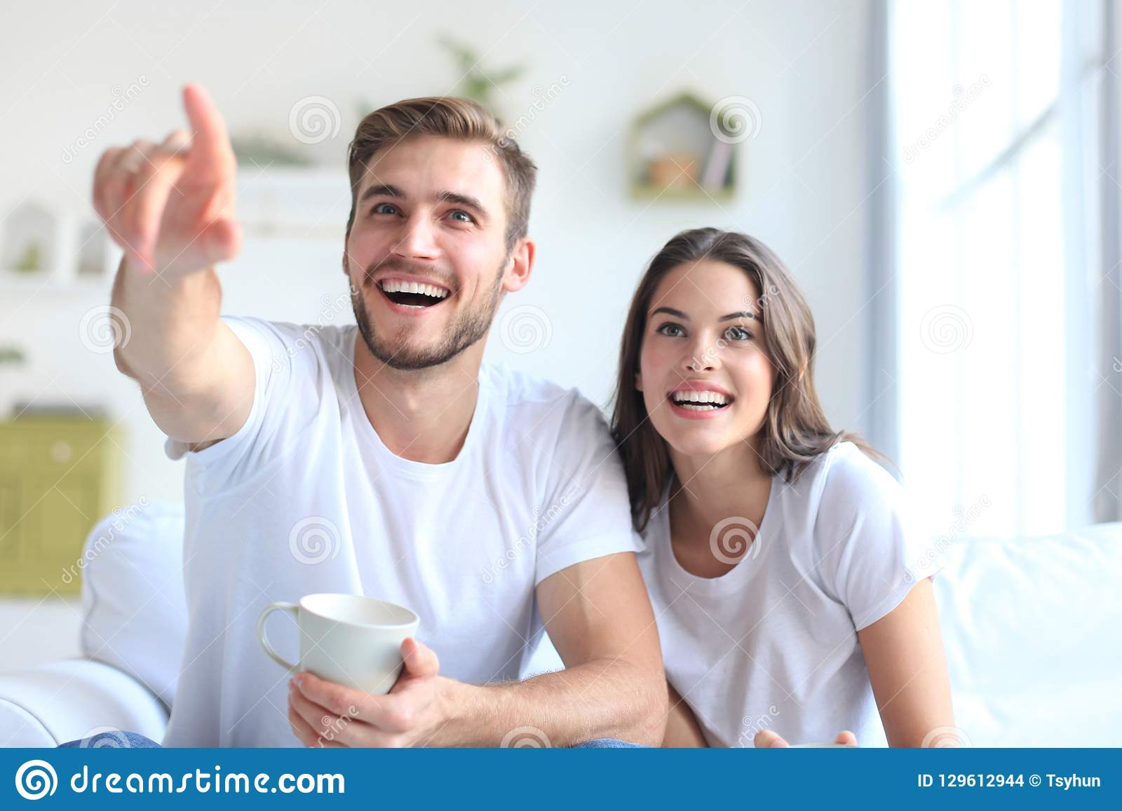 Unga älska par på tv och att skratta för soffa hemmastadd hållande ögonen på
