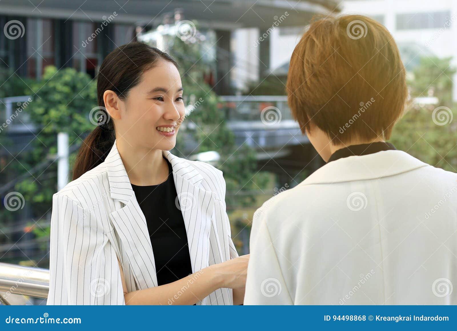 Unga affärskvinnor som hälsar med att le framsidan, affärsförhandlingmöte