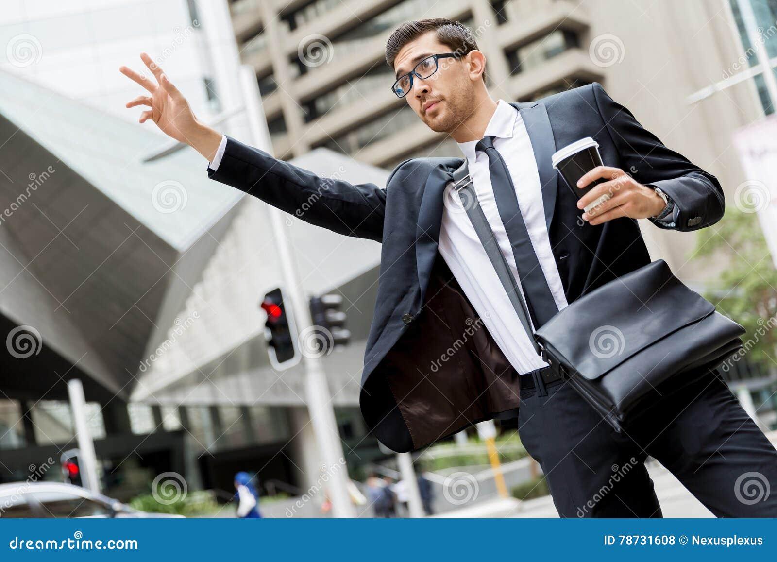 Unga affärsmän som haglar för en taxi