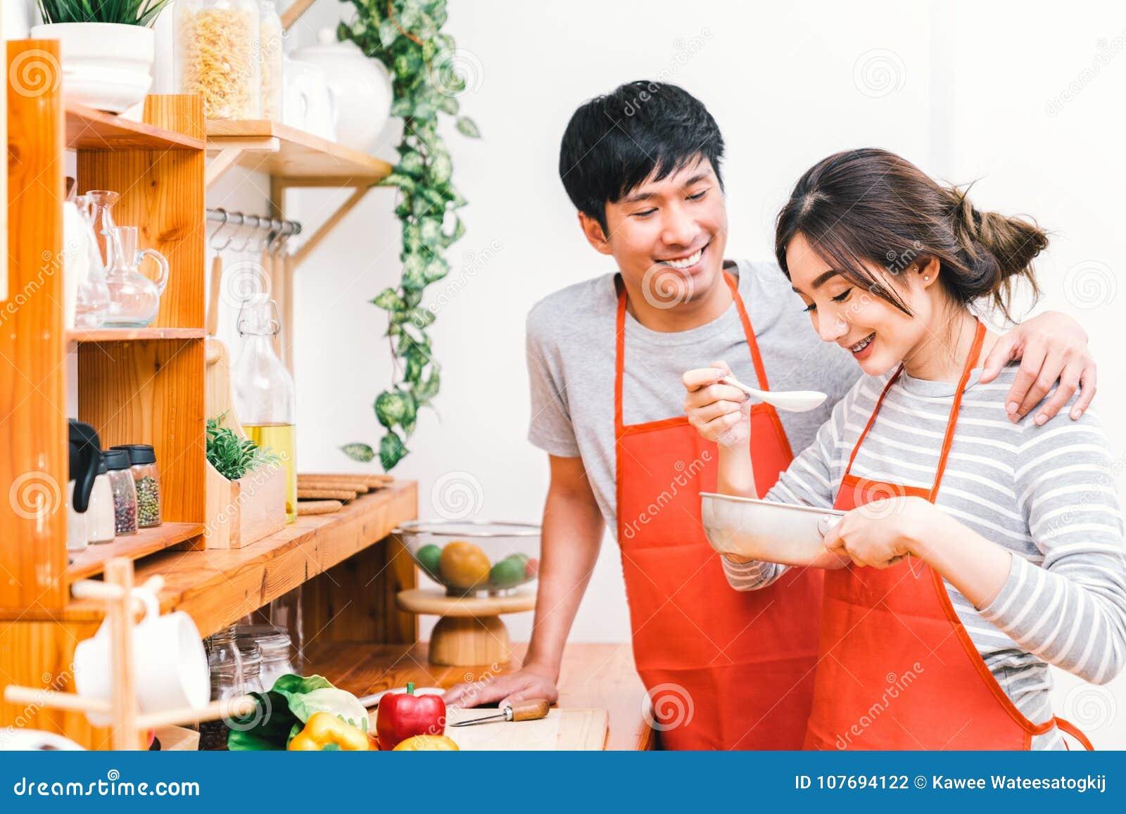 Unga asiatiska älskvärda par som tillsammans lagar mat hemmastatt kök, bär rött mål för förklädedanandelunch Flickasmaksoppa geno