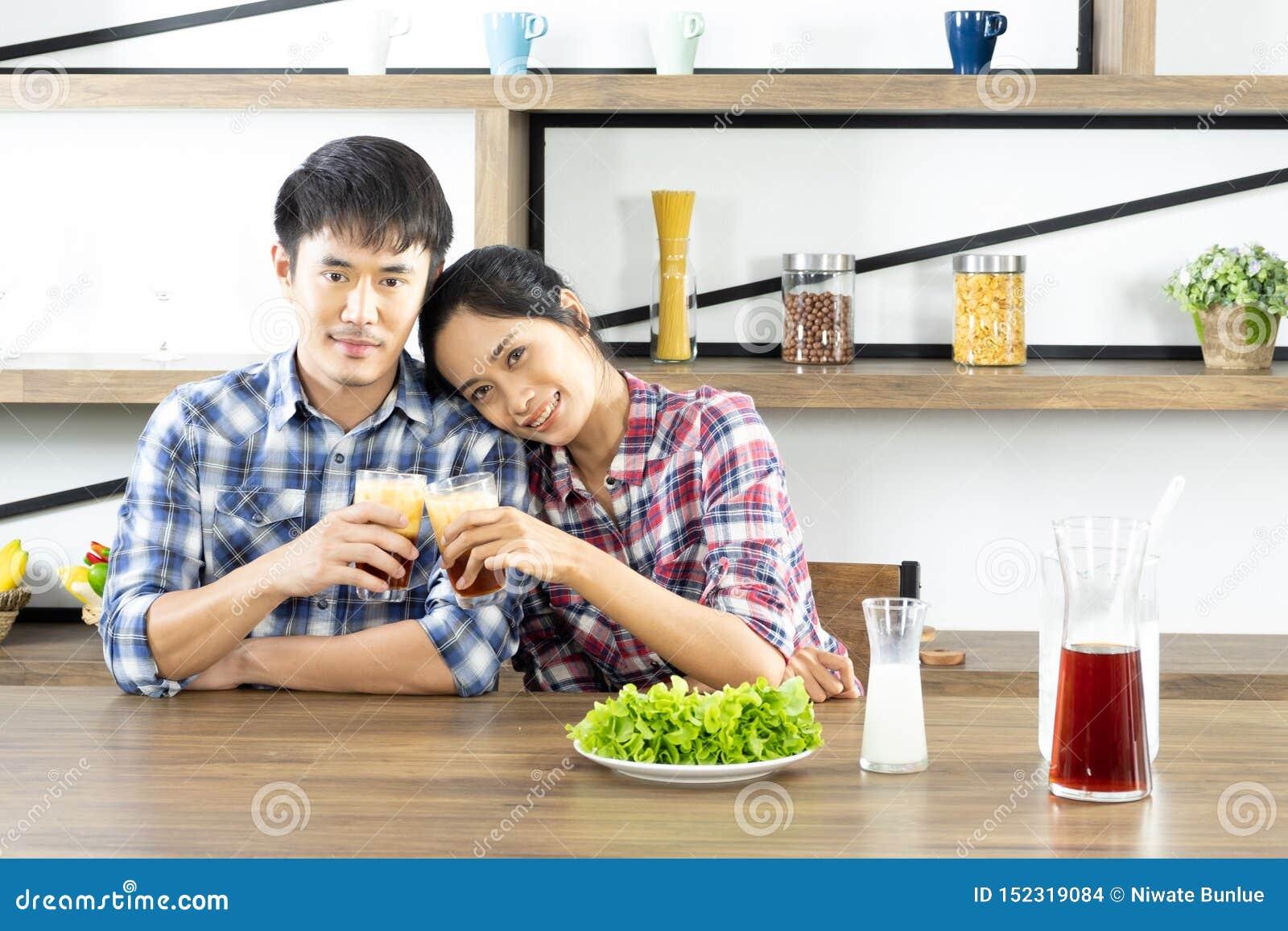 Unga asiatiska par ?r lyckliga att laga mat tillsammans, tv? familjer hj?lper sig att f?rbereda sig att laga mat i k?ket