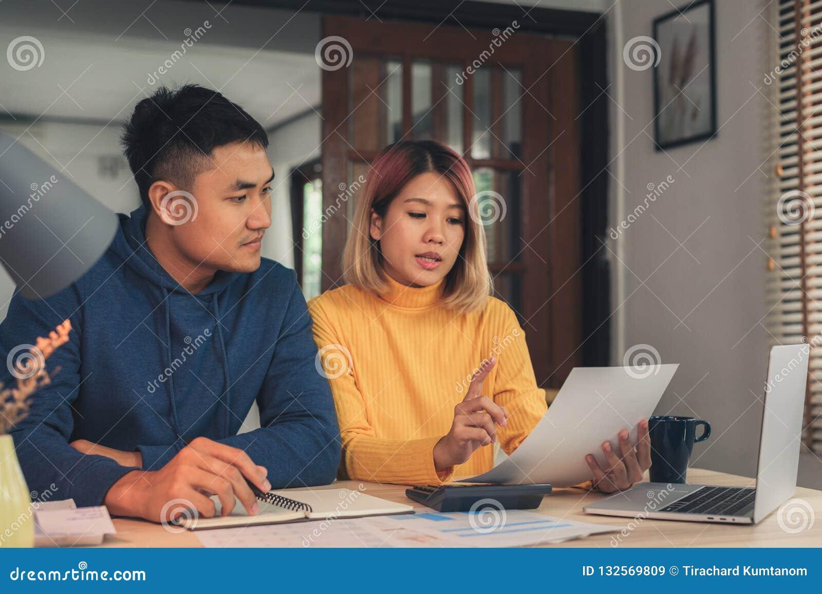 Unga asiatiska par som klarar av finanser som granskar deras bankkonton genom att använda den bärbar datordatoren och räknemaskin