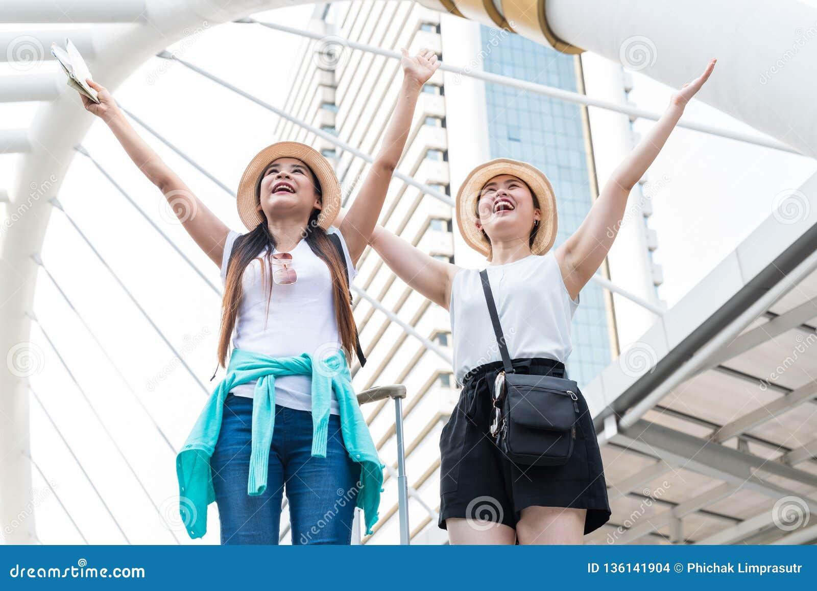 Unga asiatiska turist- kvinnor som uppåt sträcker deras armar och ser in i avstånd med att le framsidor