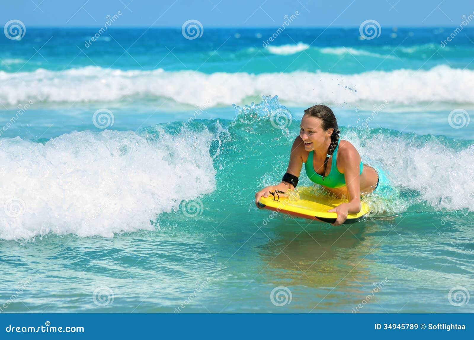 Unga attraktiva kvinnabodyboards på surfingbrädan med trevligt leende