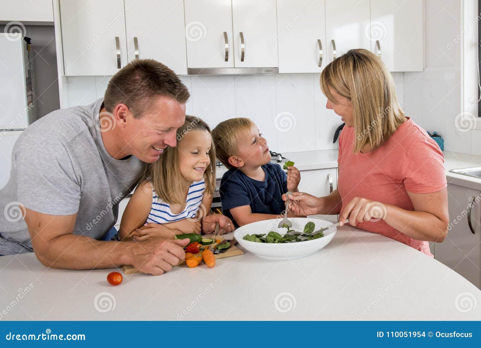 Unga attraktiva par fostrar och avlar att förbereda sallad samman med liten son och ung härlig dotter i sund vegetab