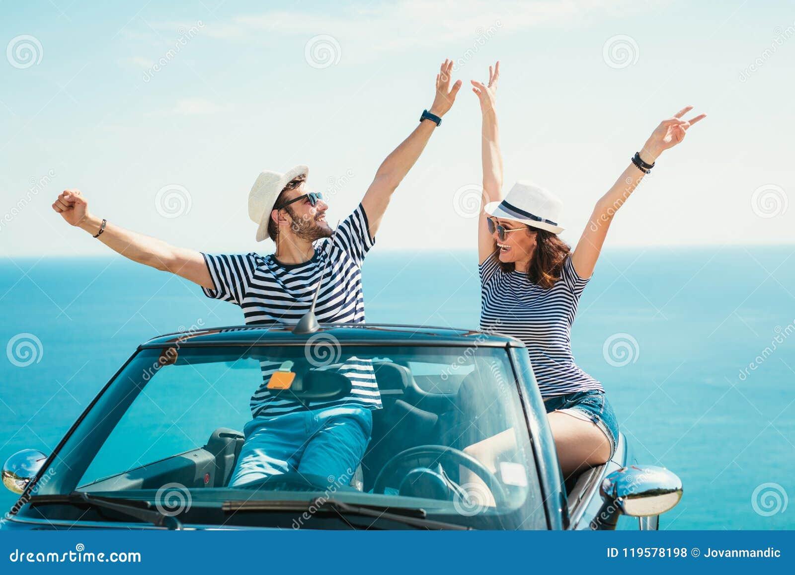 Unga attraktiva par som poserar i en konvertibel bil