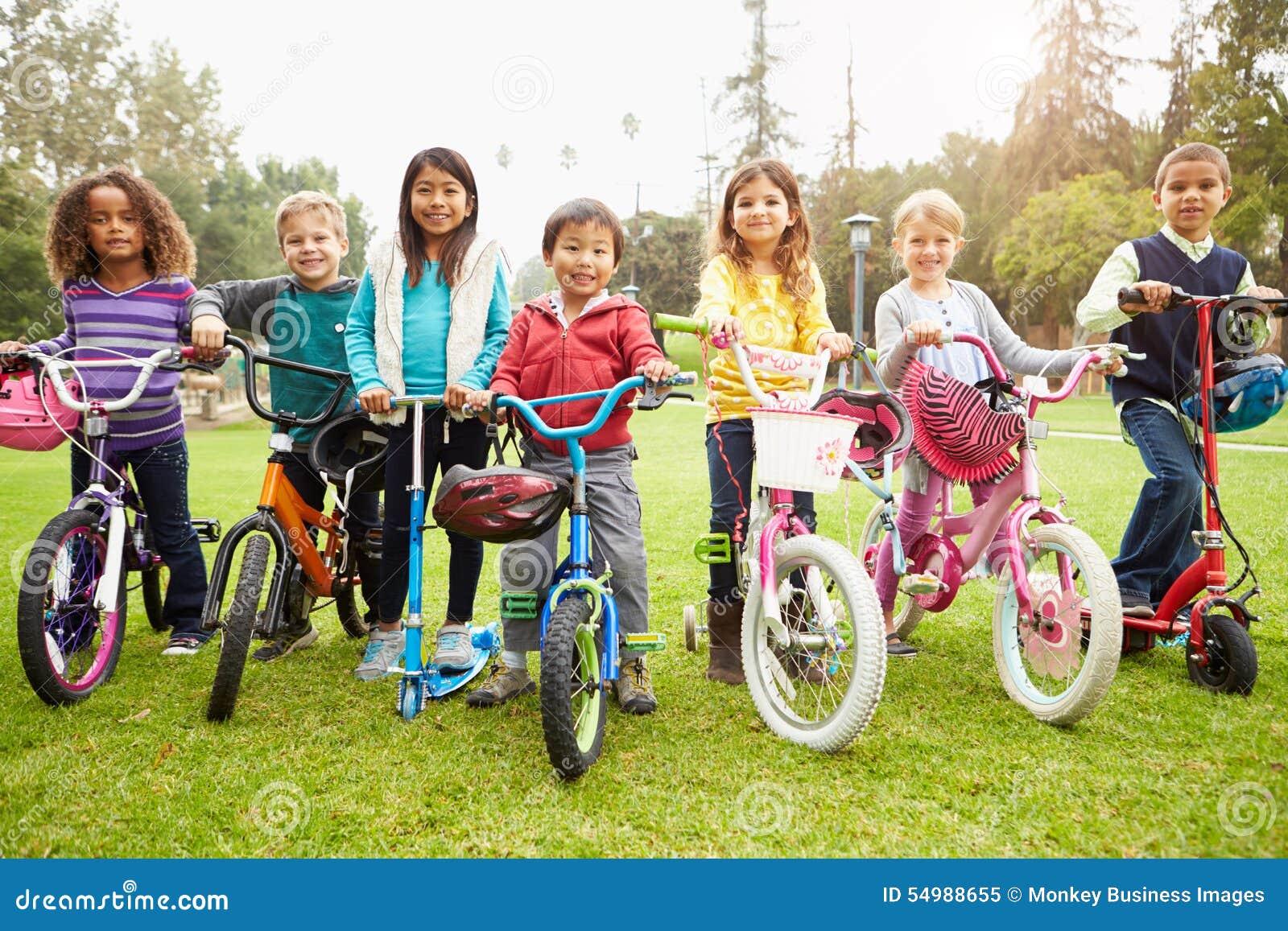 Unga barn med cyklar och sparkcyklar parkerar in