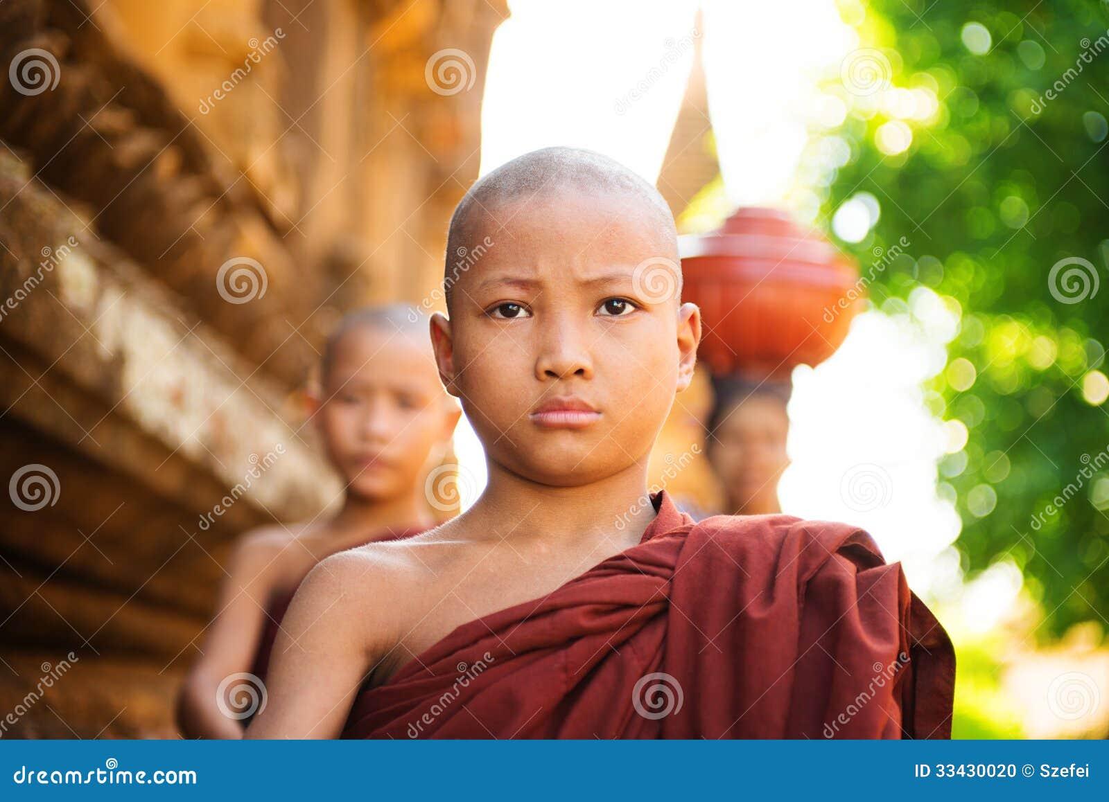 Unga buddistiska munkar som går morgonallmosa