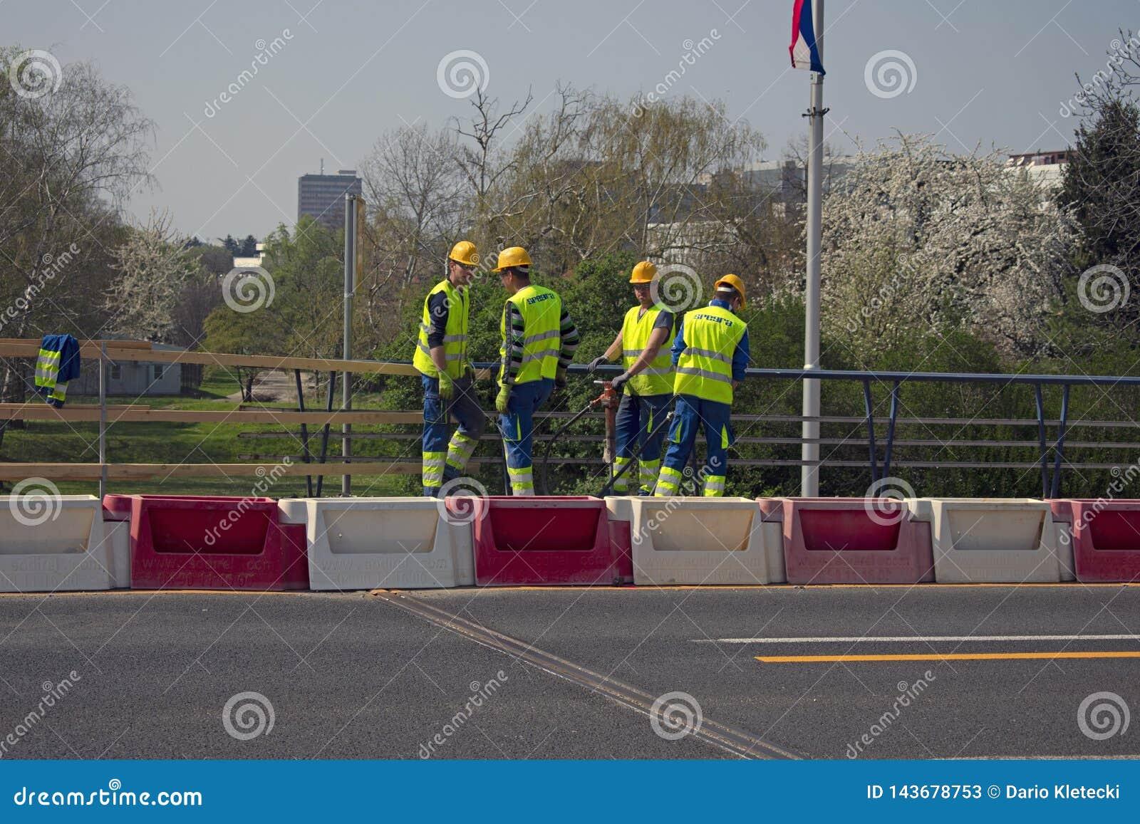 Unga byggnadsarbetare med den pneumatiska hammaren