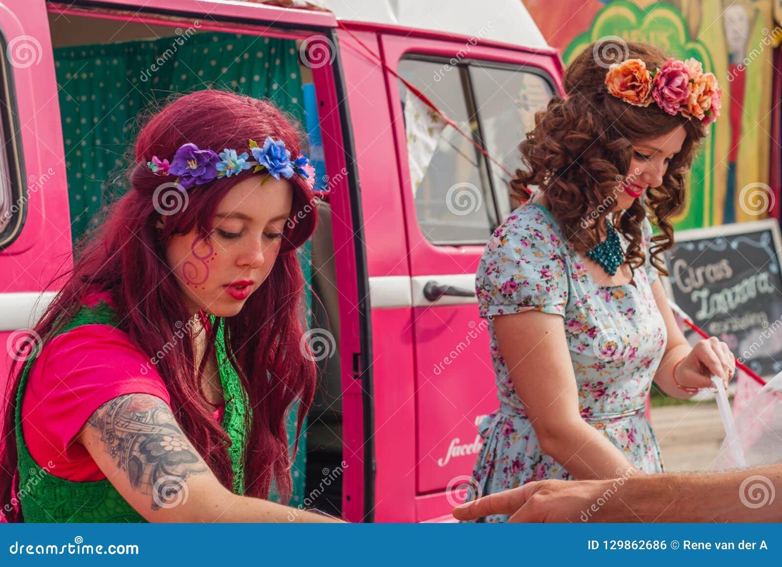 Unga damer som säljer godisen på en festival