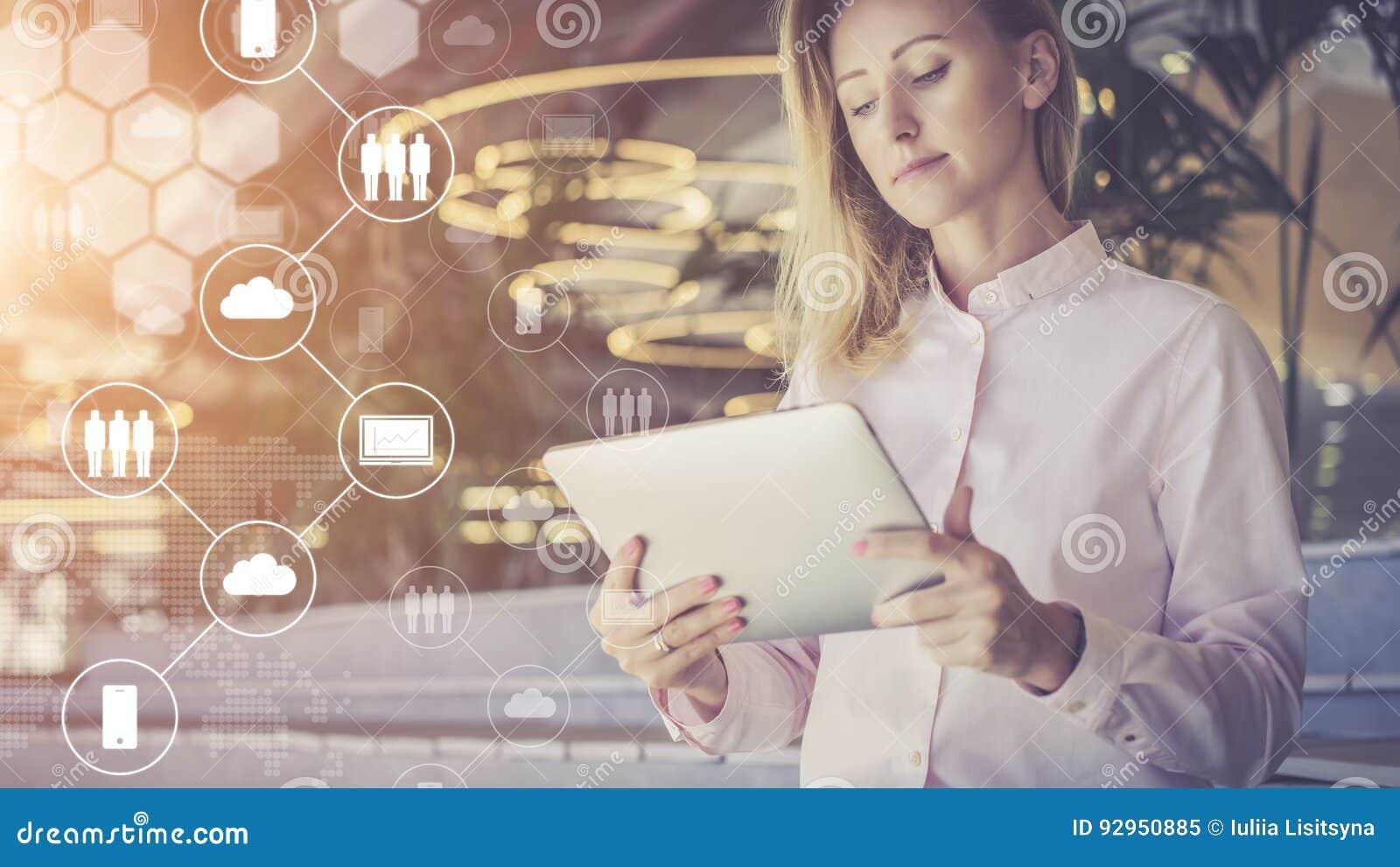 Unga digitala affärskvinnaställningar och bruk I förgrund är faktiska symboler med moln, folk, digitala grejer