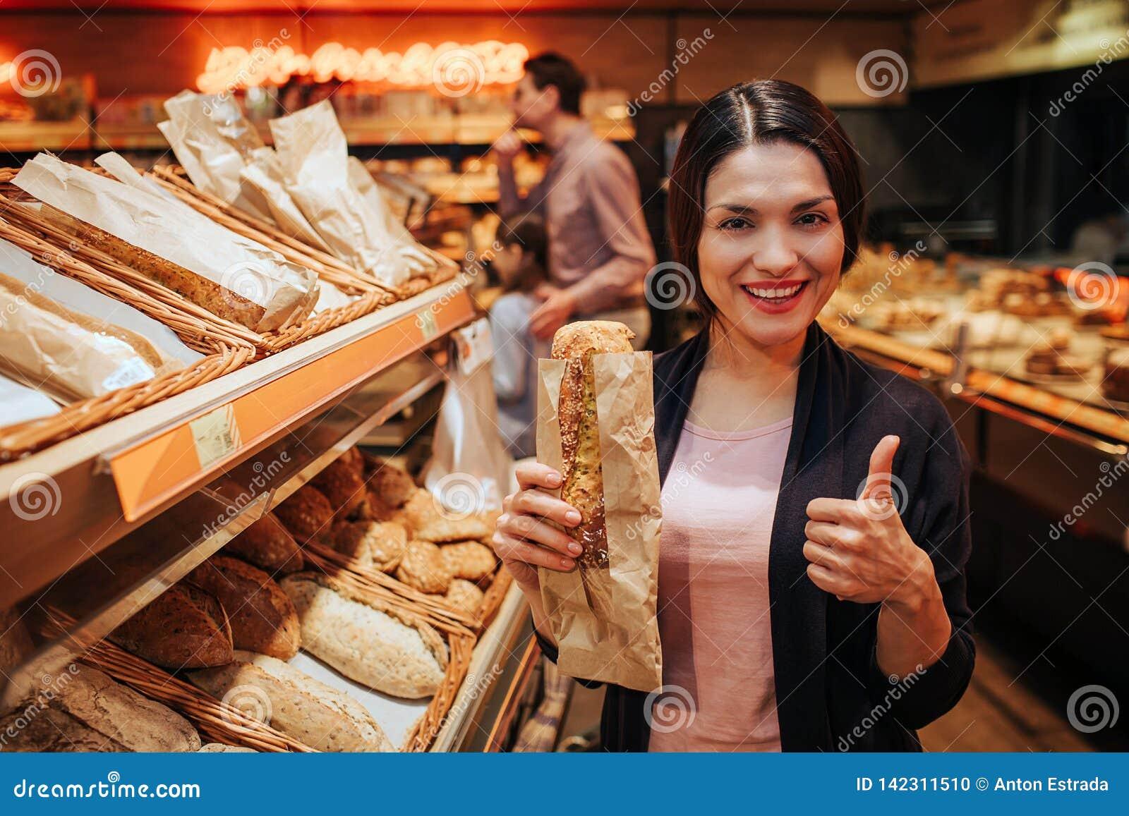 Unga föräldrar och dotter i livsmedelsbutik Positivt gladlynt kvinnahållbröd i händer och stor tumme för show upp Fathr