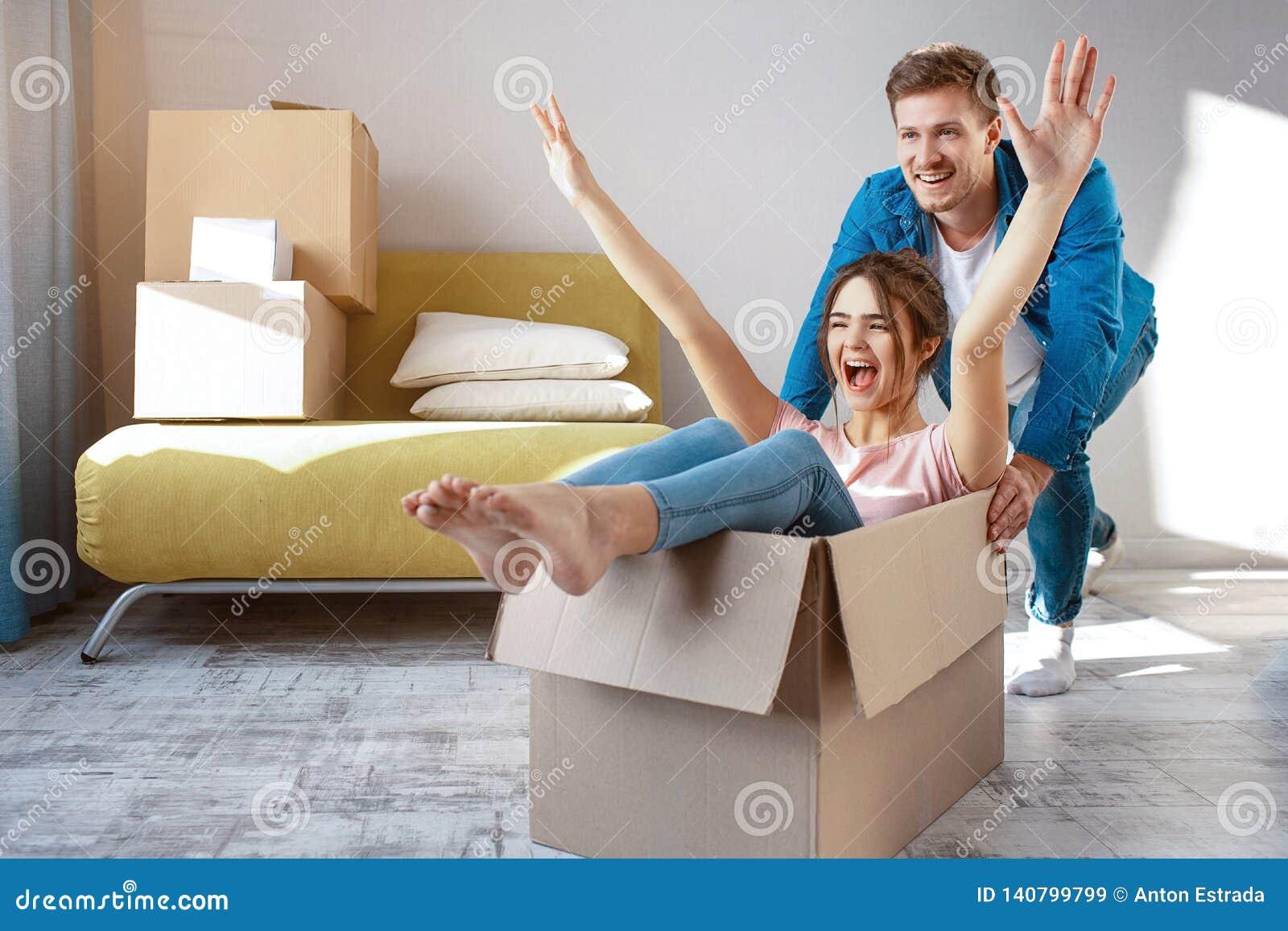 Unga familjpar köpte eller hyrde deras första lilla lägenhet Gladlynt lyckligt folk som har gyckel Hon sitter i ask och
