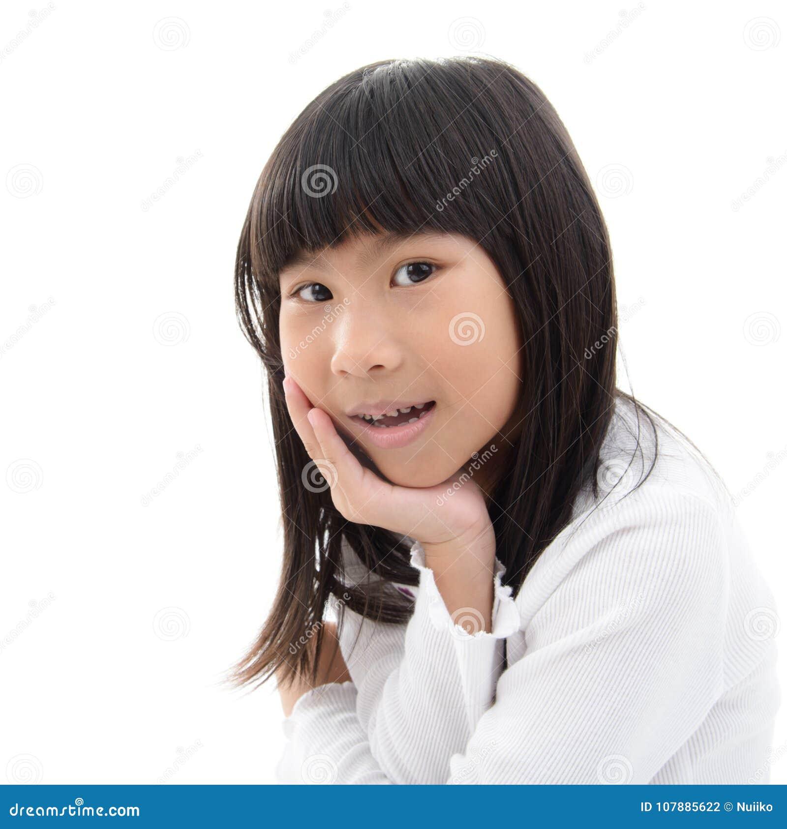 Unga flickan grinar med hennes haka i henne händer