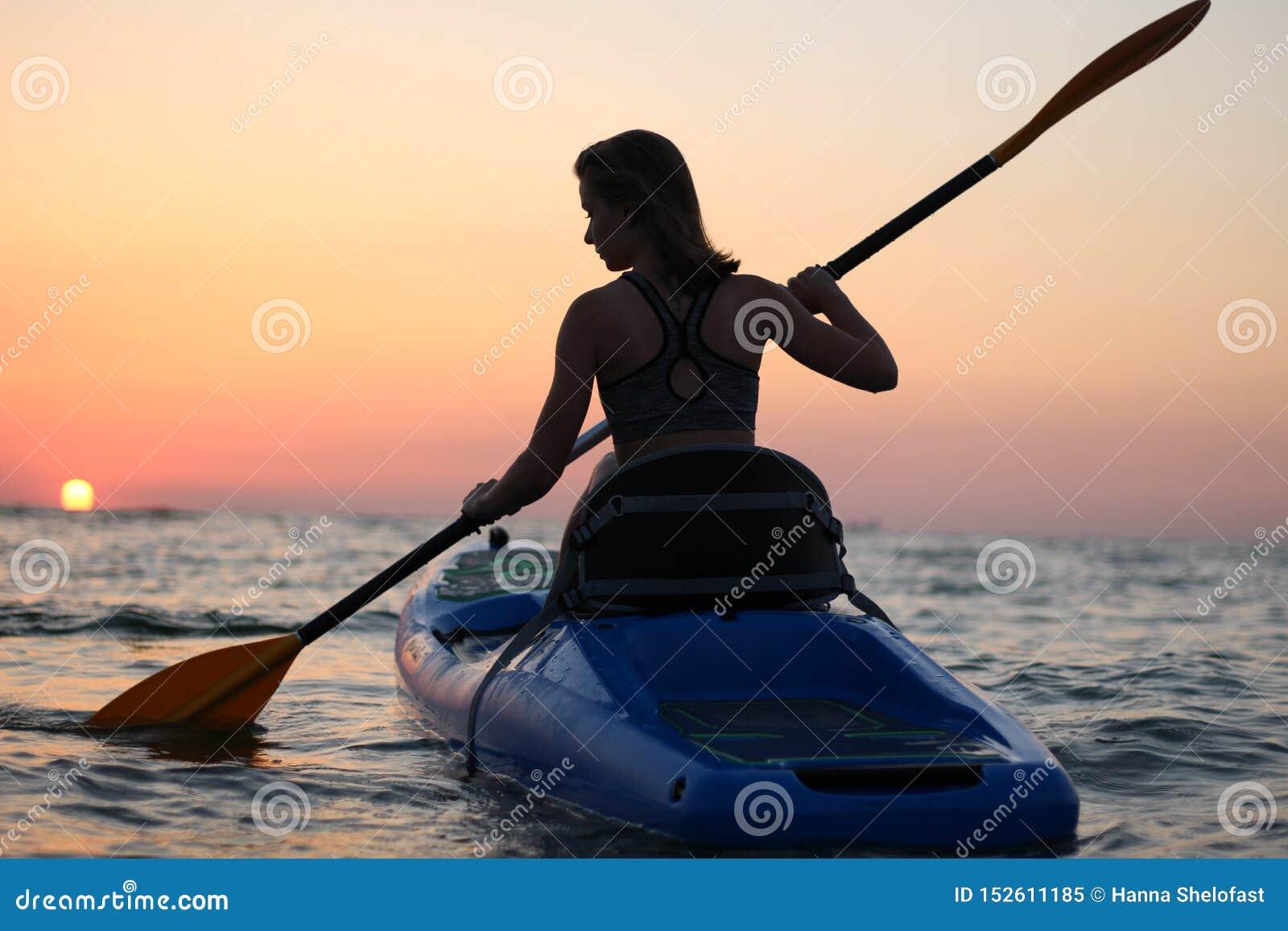 Unga flickan på kajaken hälsar gryningen av solen