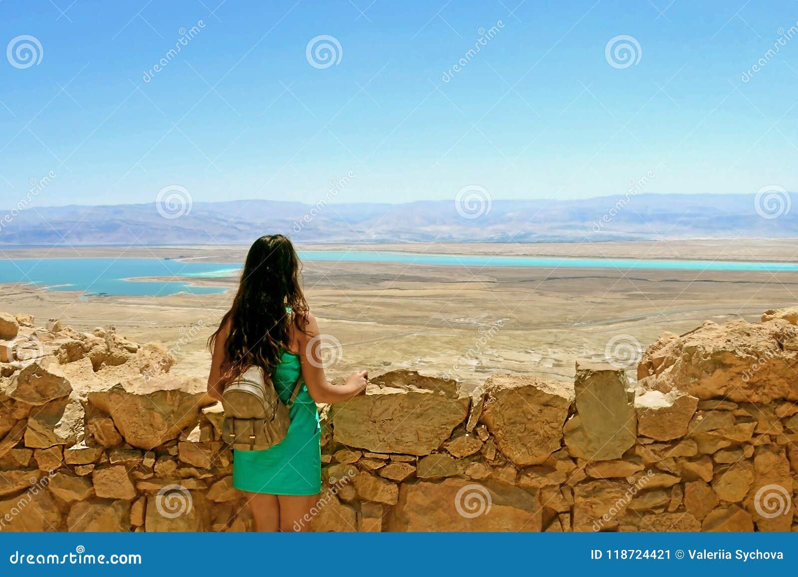 Unga flickan ser det döda havet Fördärvar av den Herods slotten i den Masada fästningen i Israel