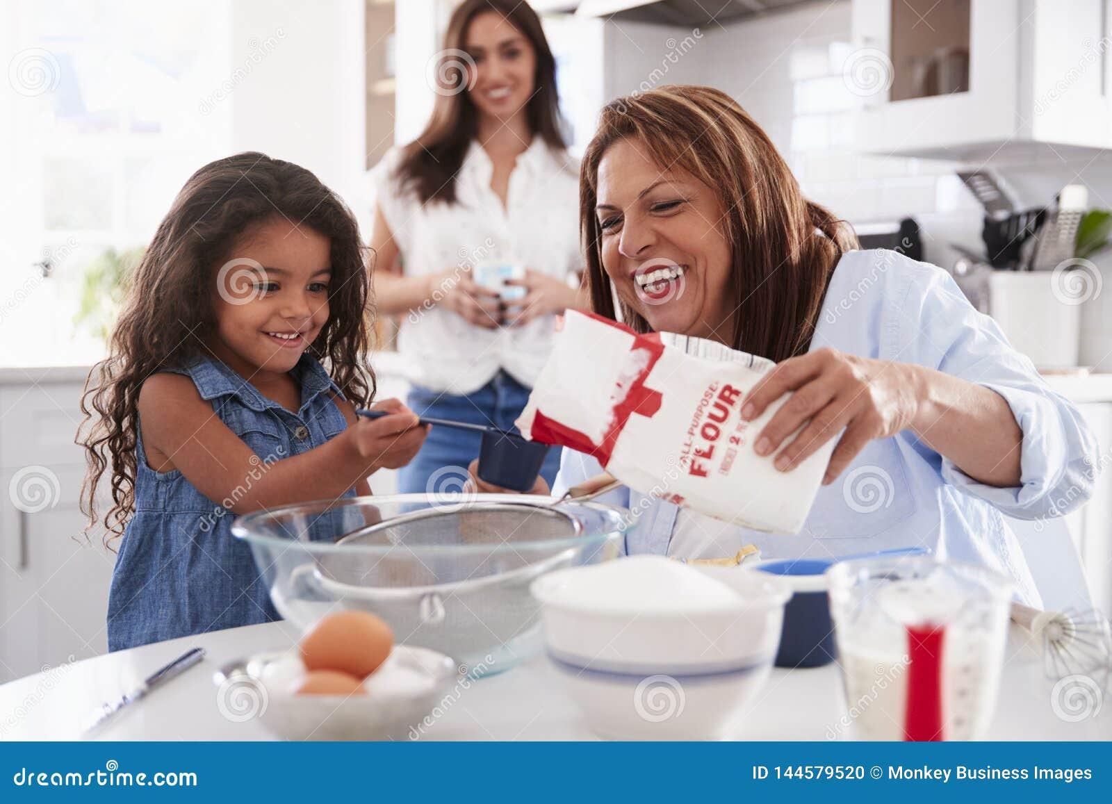 Unga flickan som gör en kaka i köket med hennes farmor, mum står hålla ögonen på, den selektiva fokusen