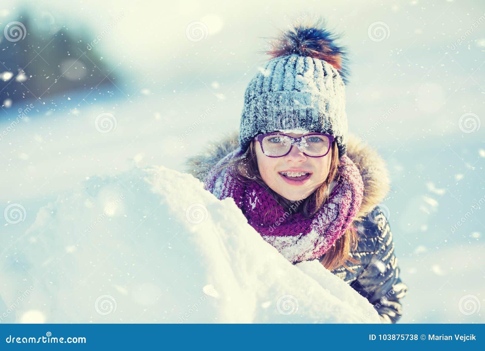 Unga flickan spelar med snö Lycklig flicka Blowin för skönhetvinter