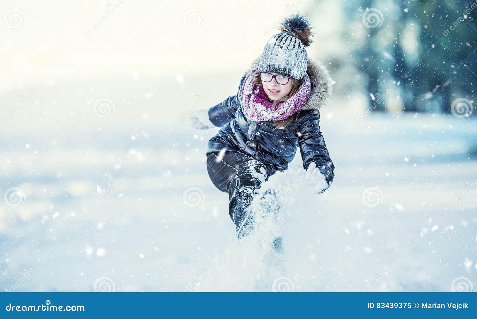 Unga flickan spelar med snö Parkerar den lyckliga flickan för skönhetvintern som blåser insnöad frostig vinter, eller utomhus