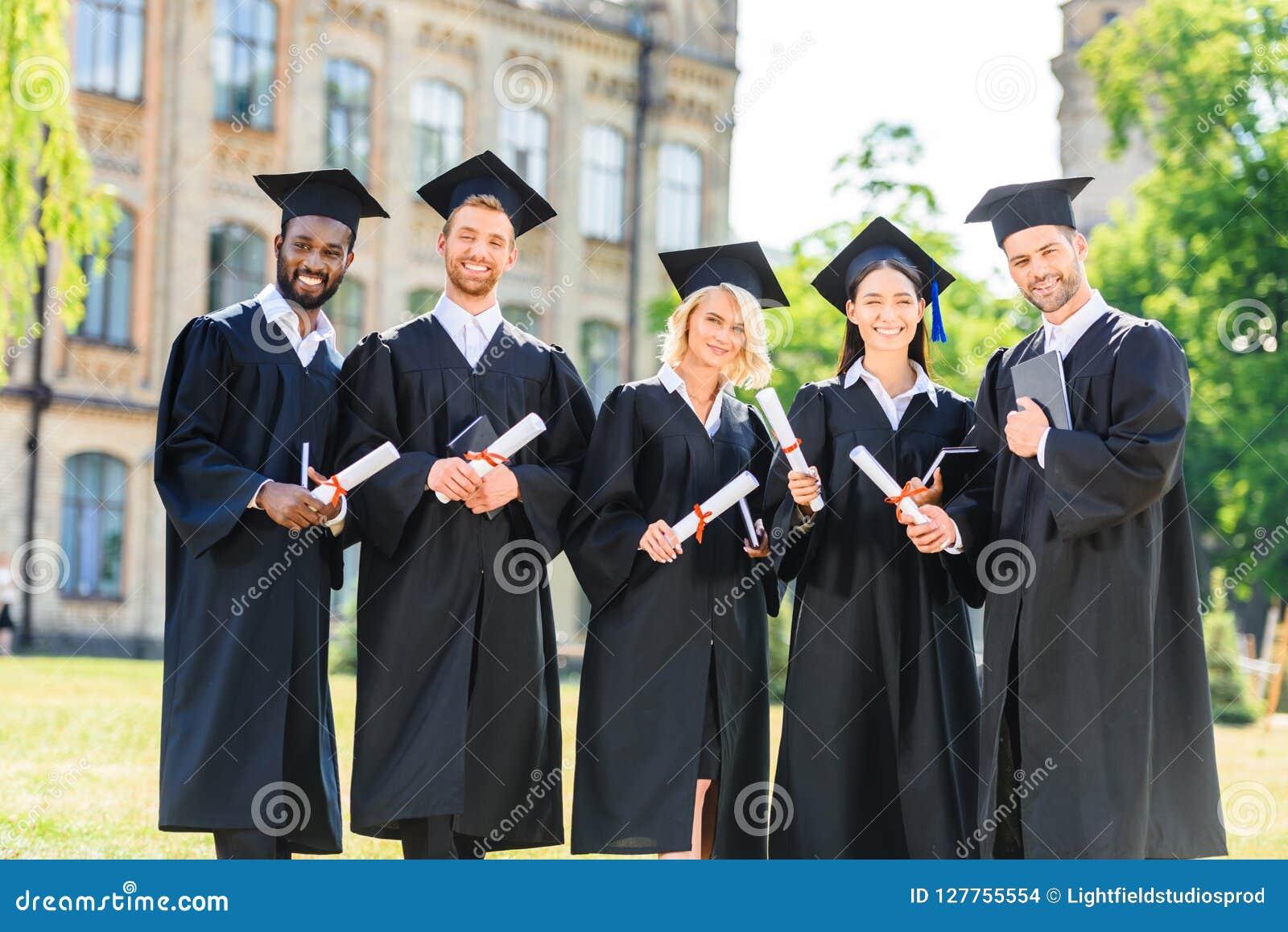 Unga graderade studenter i uddar som rymmer diplom och att se