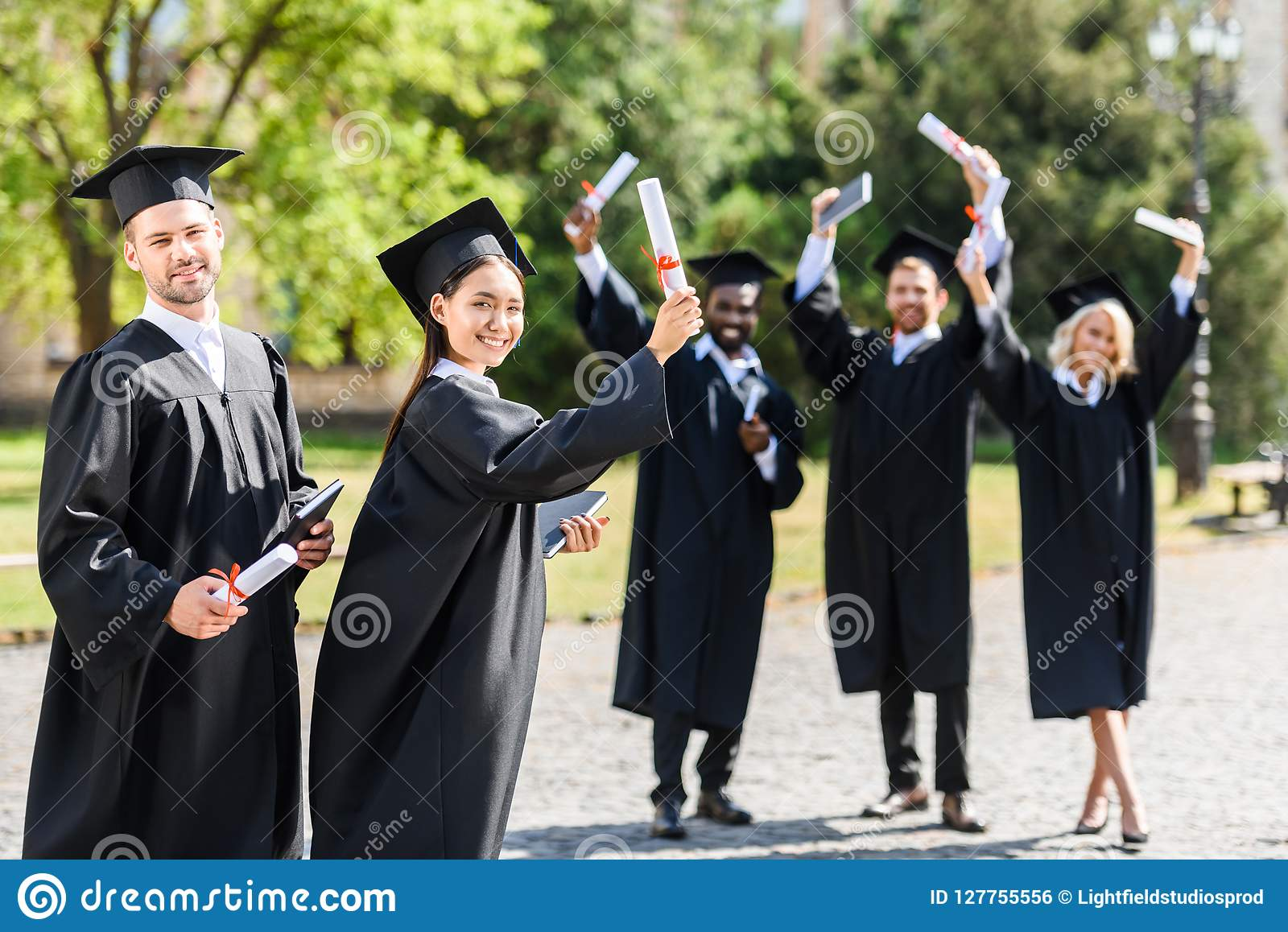 Unga graderade studenter som tillsammans står, i trädgård och att se för universitet