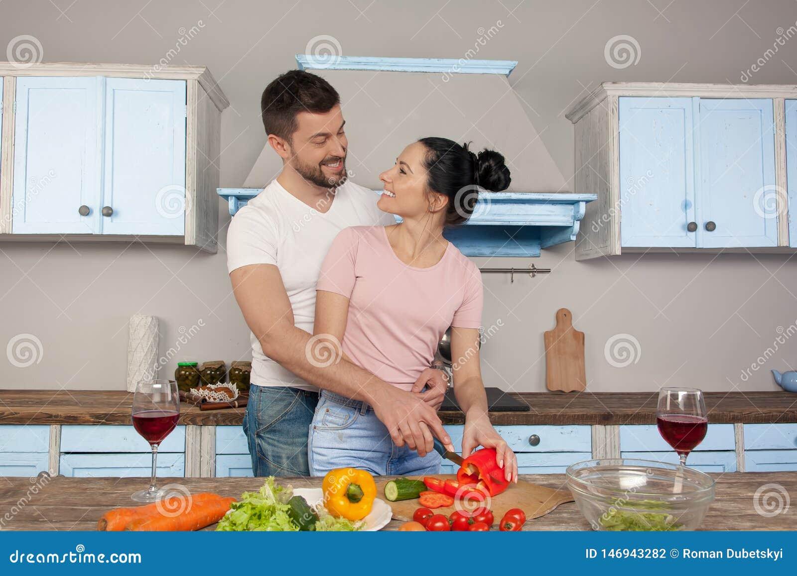 Unga härliga par som kramar i köket som tillsammans lagar mat en sallad De ler p? de