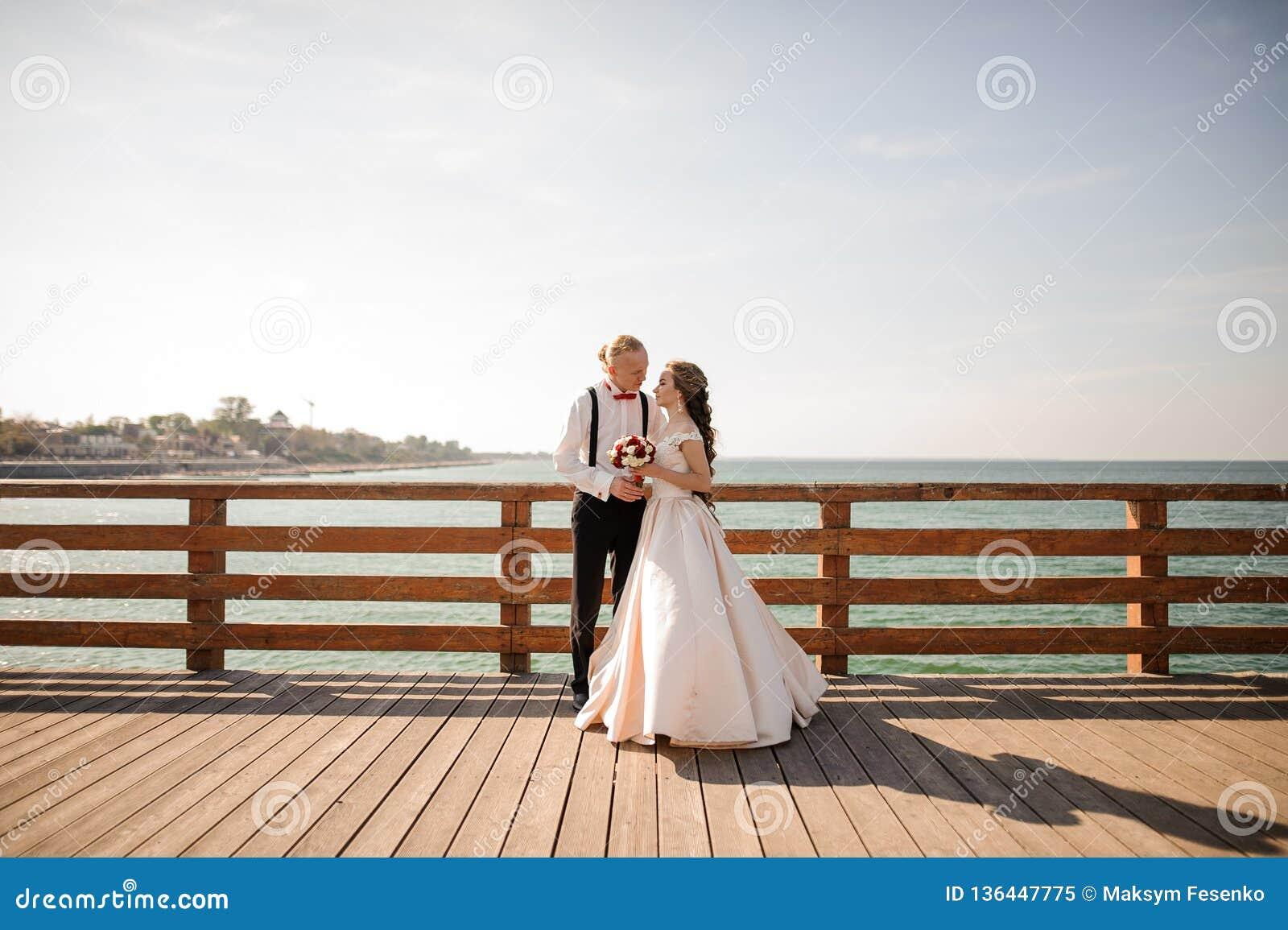 Unga härliga par som omfamnar på träbron i bakgrund av havet