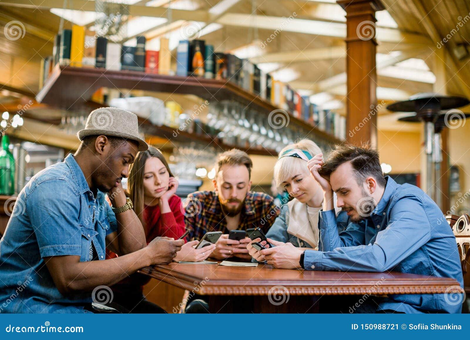 Unga högskolestudenter eller coworkers som tillsammans använder smartphones på coffee shop, olik grupp Tillf?llig aff?r, frilans