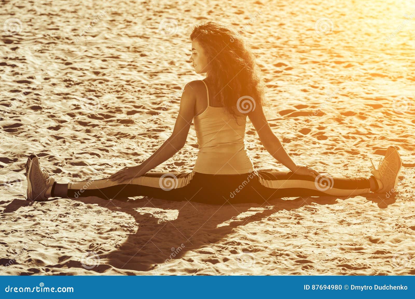 Unga idrottsman nen - gymnast med lockigt hår och gymnastikskor som gör splittringarna på stranden i sommarmorgonövning