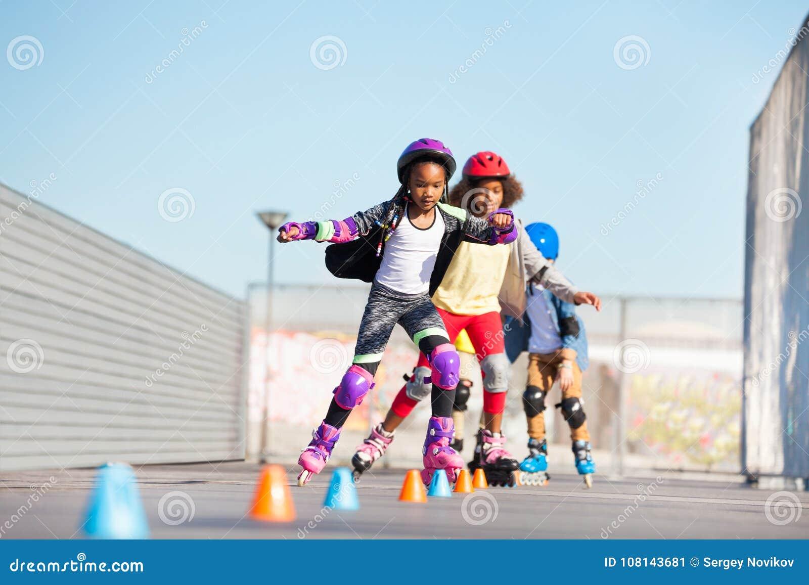 Unga inline skateboradåkare som gör trick på skridskon, parkerar
