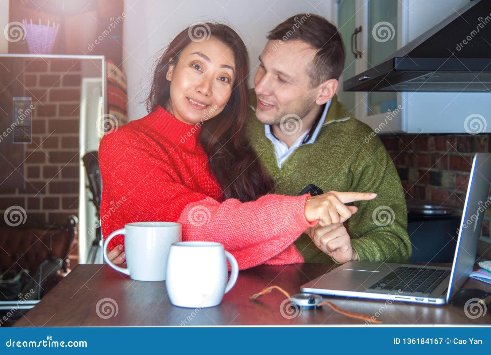 Unga intressanta par som hemma ser en bärbar dator i köket och rymmer en smartphone Ett internationellt par på det inter-