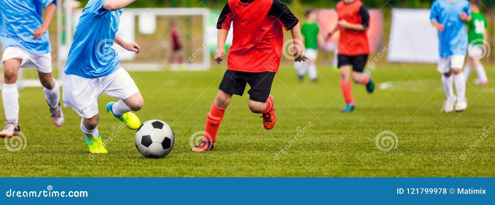 Unga Junior Football Match Spelare som kör och sparkar Footbal