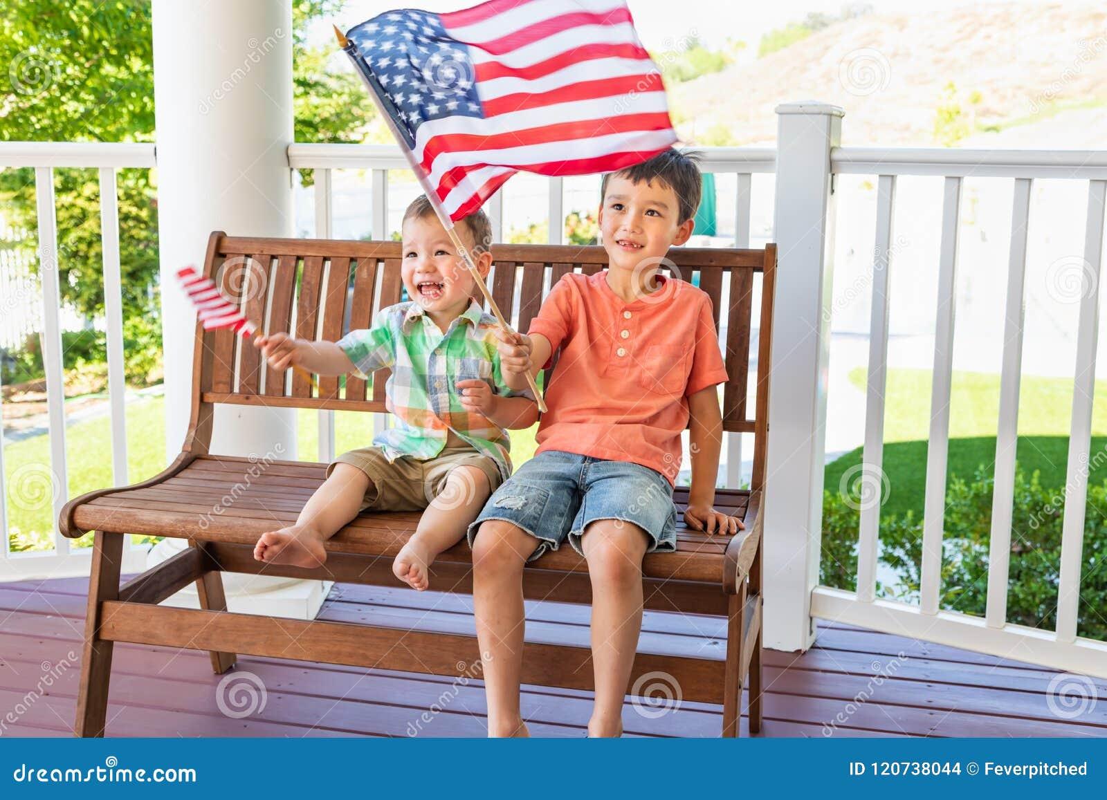 Unga kinesiska Caucasian bröder för blandat lopp som spelar med amerikanska flaggan