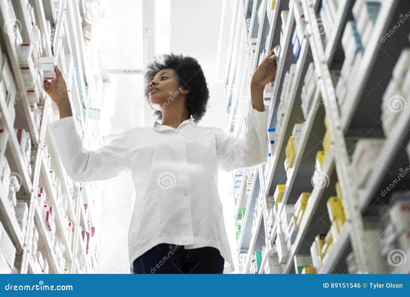 Unga kvinnliga kemistArranging Stock In hyllor på apotek