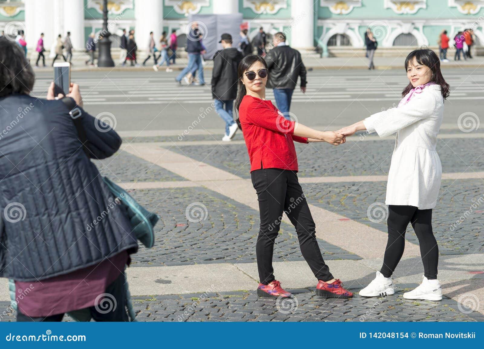 Unga kvinnor av det asiatiska utseendet fotograferas på slottfyrkant mot bakgrunden av eremitboningen i St Petersburg,