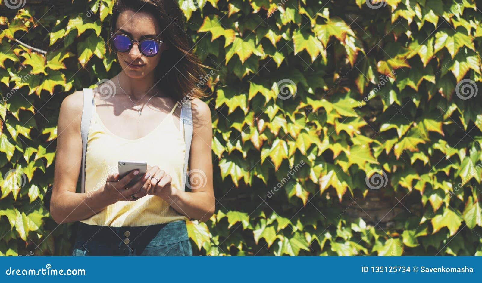 Unga kvinnor för stående i solglasögon genom att använda upp den smarta telefonen på för naturvägg för bakgrund grön åtlöje, kvin