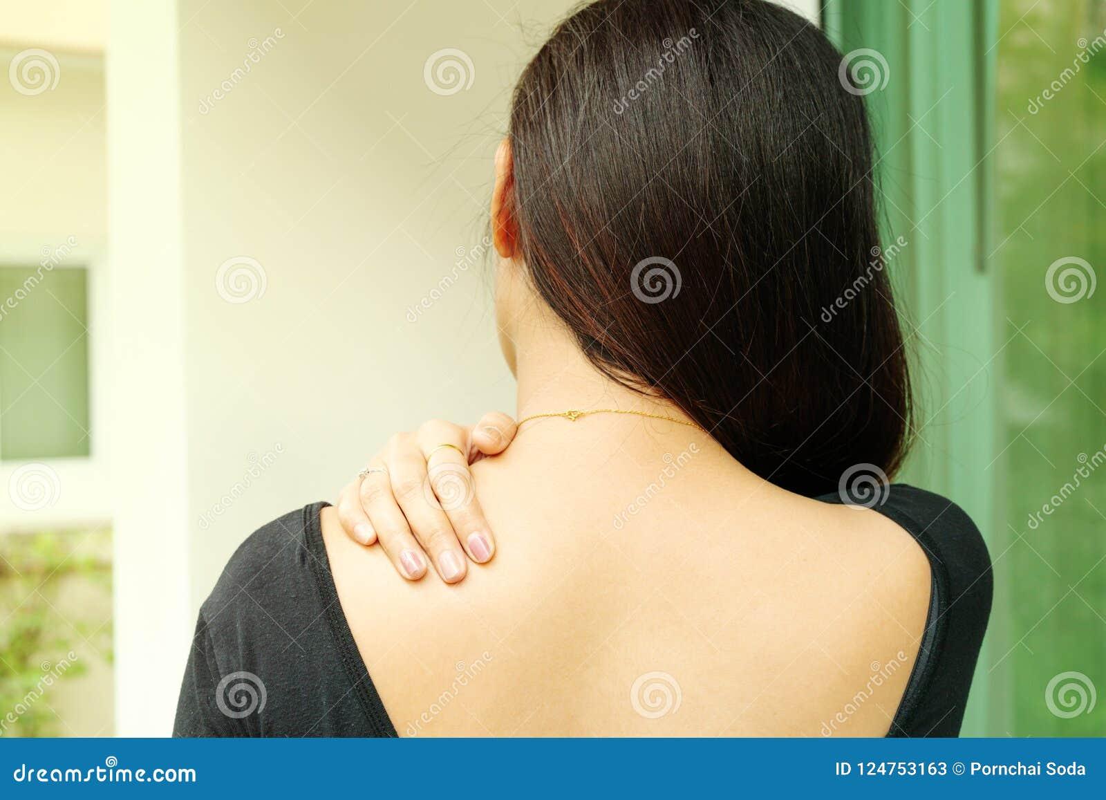 Unga kvinnor hånglar, och skuldran smärtar skada-, sjukvård- och läkarundersökningbegrepp