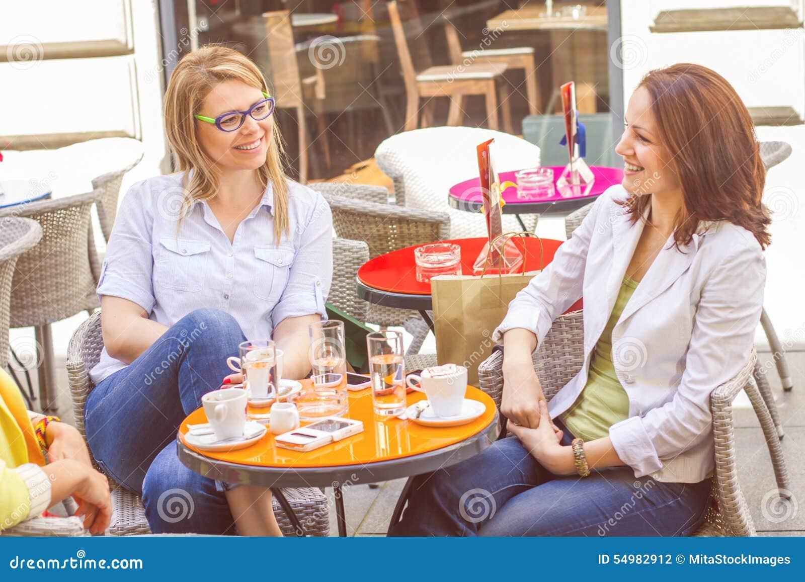 Unga kvinnor har kaffeavbrottet tillsammans