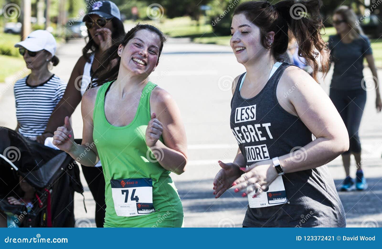 Unga kvinnor ler på kameran på loppet för vägen 5K
