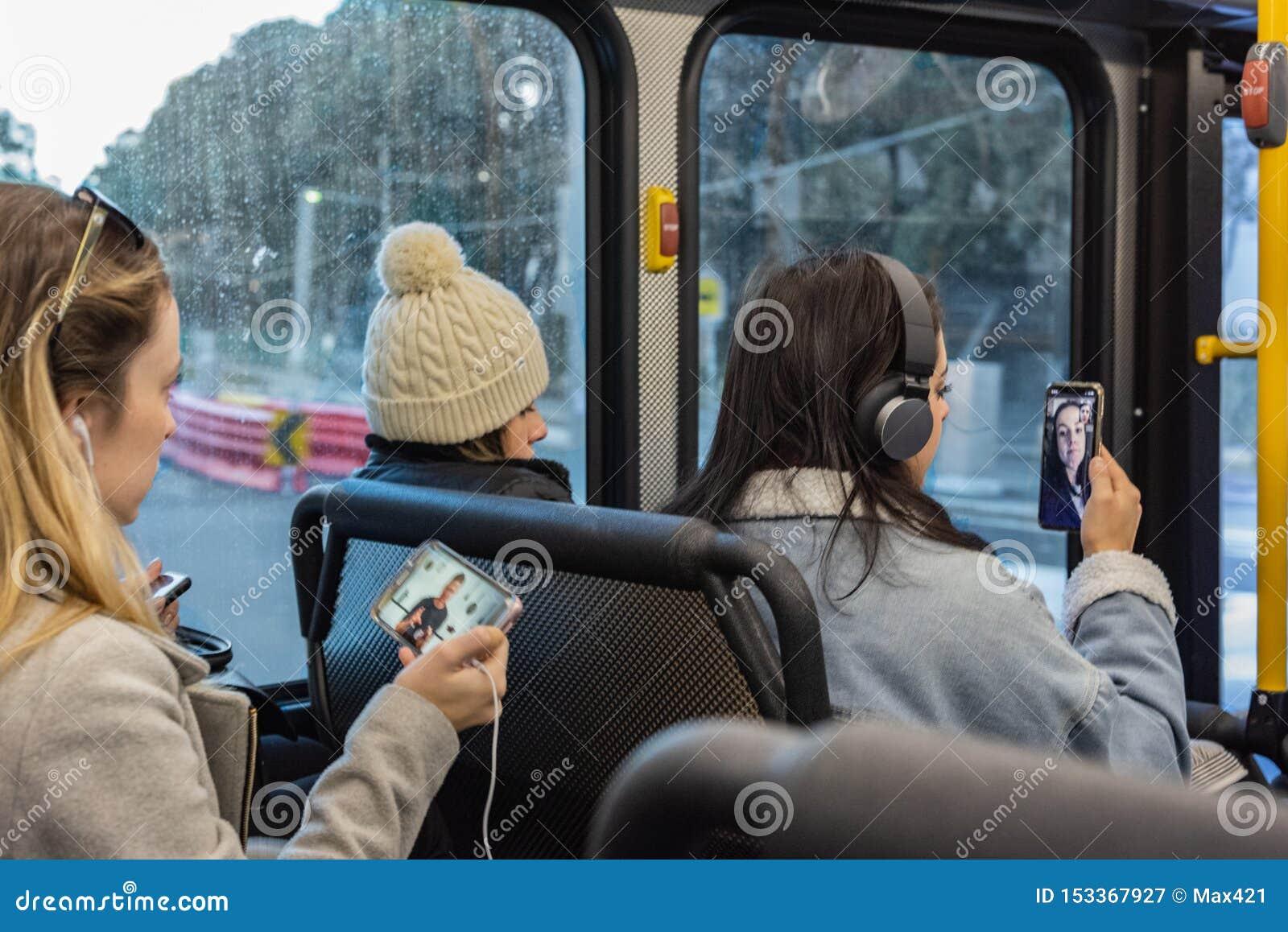 Unga kvinnor meddelar med deras mobila enheter på bussen