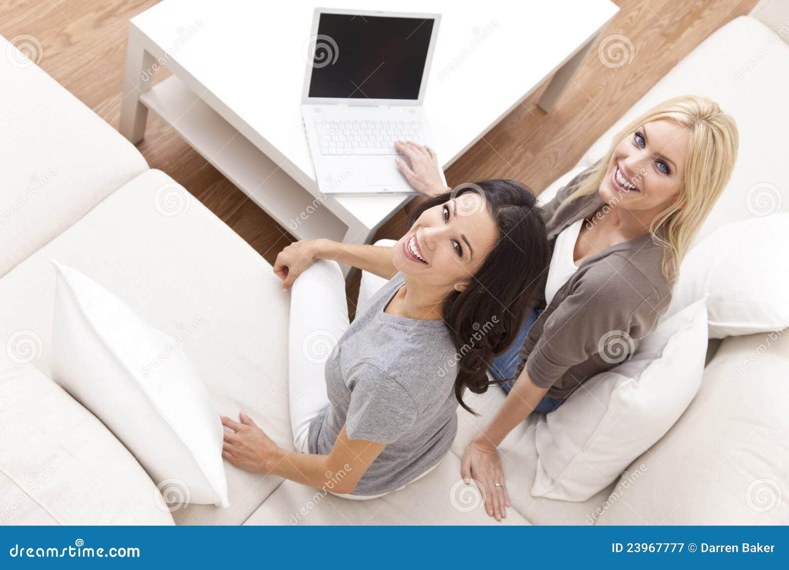 Unga kvinnor som hemma använder bärbar datordatoren på sofaen