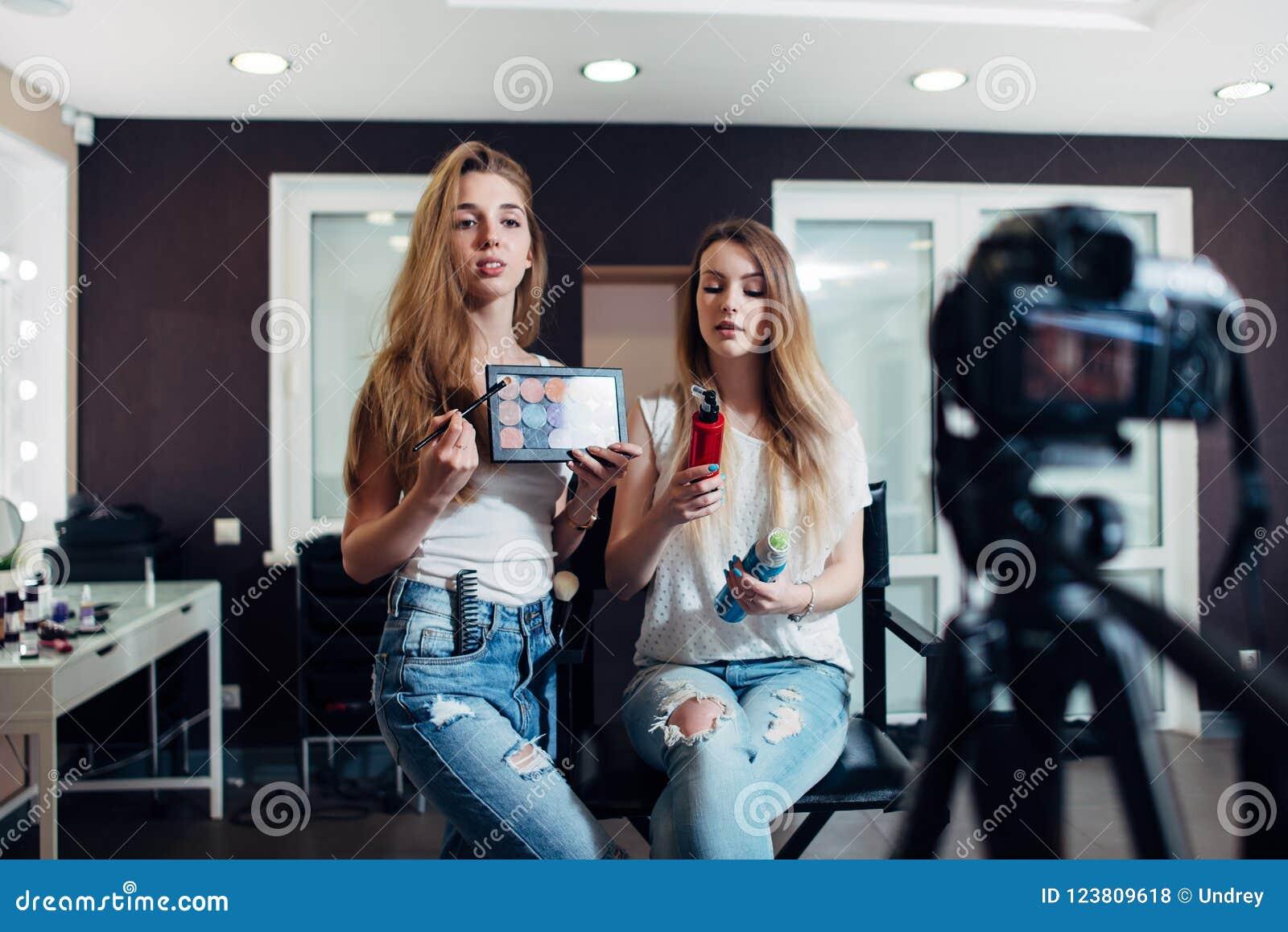 Unga kvinnor som rymmer skönhetsprodukter som gör en video på skönhetsmedel för videoblog